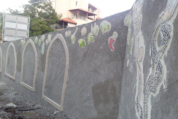 הדבקת גפן הפסיפס לקיר. מסגרות אבן מודבקות מסביב למקום המיועד לתמונות הפסיפס.