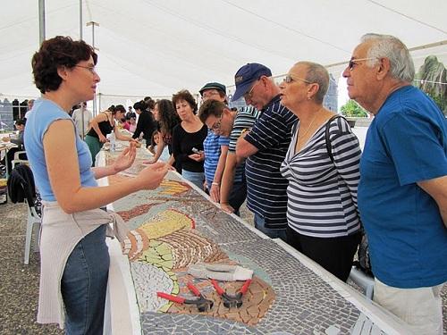 תיירים מקבלים הסבר על הפרויקט ועל עבודת הפסיפס