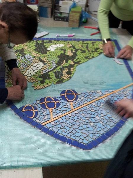 קבוצת הנשים עובדת במרץ, בשיתוף פעולה ובהנאה על יצירת הפסיפס