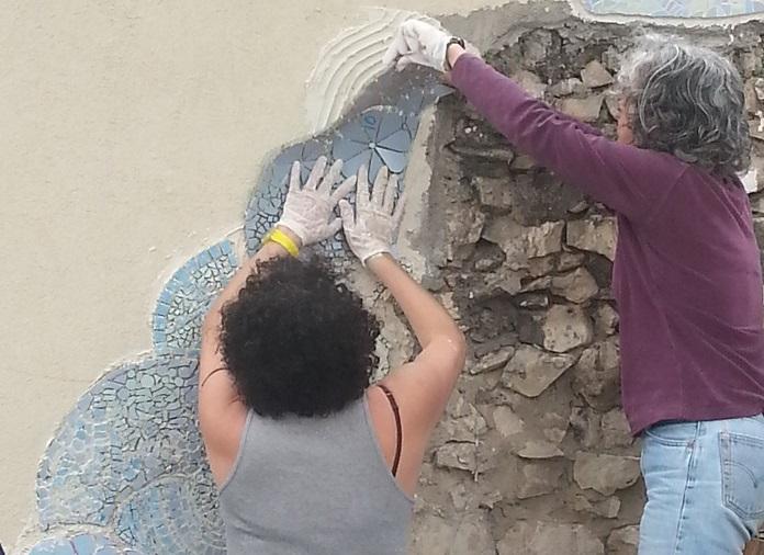 הדבקת מסגרת הפסיפס לקיר האבן.