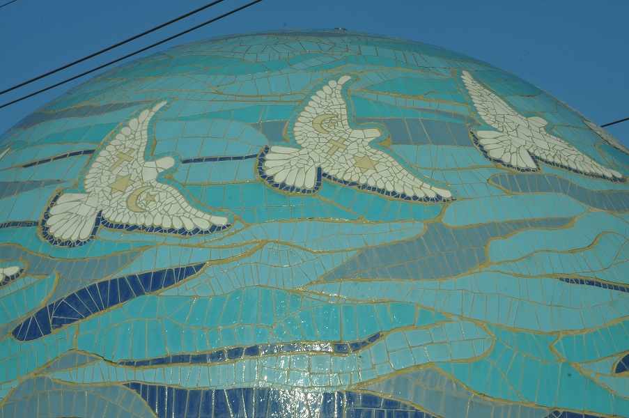 פסיפס קרמיקה. יונת השלום ובתוכה סמלי שלוש הדתות. מים זורמים על כיפת הפסיפס.