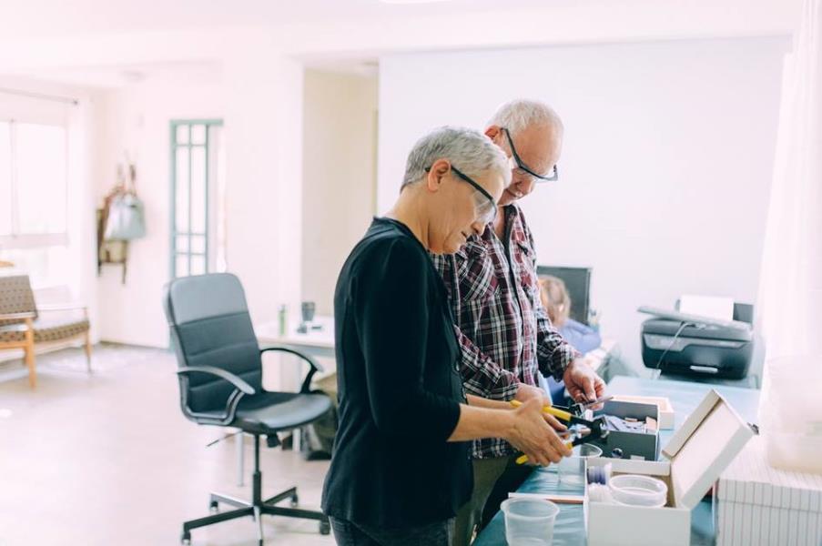 יום הולדת 60 לאבא. כל המשפחה יוצרת יחד: בני הזוג עובדים על שולחן הפסיפס בשיתוף פעולה